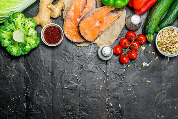 Здоровая пища. стейки лосося с органическими овощами и орехами на темном деревенском столе.