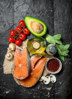 Здоровая пища. стейки из лосося с овощами, зеленью и специями. на черном деревенском фоне.