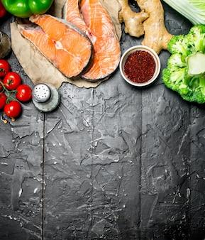 Здоровая пища. стейки из лосося с овощами, зеленью и специями на темном деревенском столе.