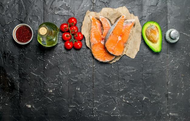Здоровая пища. лосось с натуральными продуктами. на черном деревенском фоне.