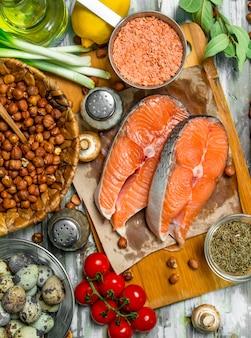 건강한 음식. 유기농 야채, 과일, 견과류와 연어. 소박한 배경.