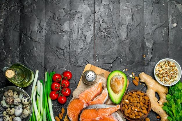 Здоровая пища. лосось с овощами и зеленью. на черном деревенском фоне.