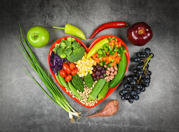 健康食品の選択は、心生活コレステロールダイエット健康概念のきれいな食事。新鮮なサラダフルーツと緑の野菜は、健康食品ビーガンの赤いハートプレートにさまざまな豆ナッツ穀物を混合