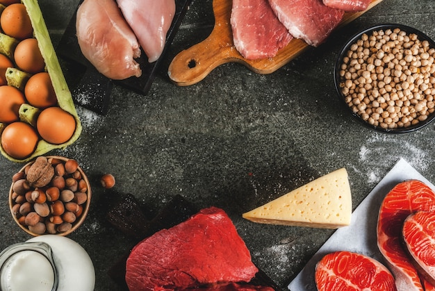 Healthy food . selection of protein sources: beef and pork meat, chicken  filet, salmon fish, egg, beans, nuts, milk. top view copyspace, dark background frame