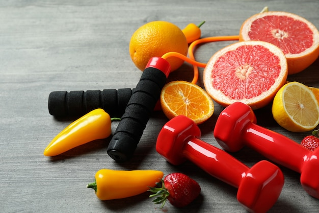 Здоровая еда, скакалка и гантели на сером текстурированном фоне