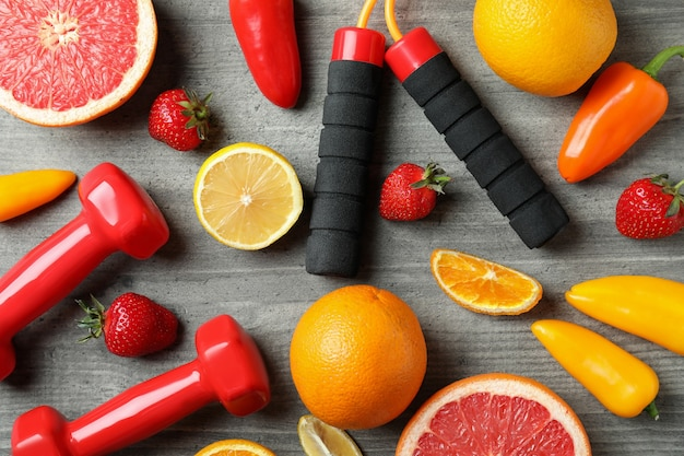 Healthy food, skipping rope and dumbbells on gray textured background