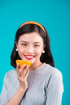 Здоровая пища. улыбаясь милые девушки кинозвезды азиатские держа апельсин на синем фоне.