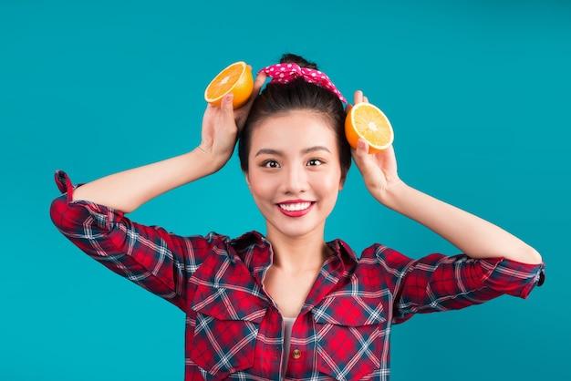 健康食品。青い背景の上にオレンジを保持している素敵なピンナップアジアの女の子を笑顔。