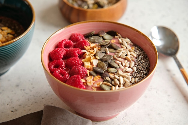 Healthy food - smoothie bowl topped with raspberries, granola, seeds and chia.
