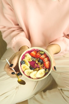 Healthy food smoothie bowl with berries and granola in woman's hands.