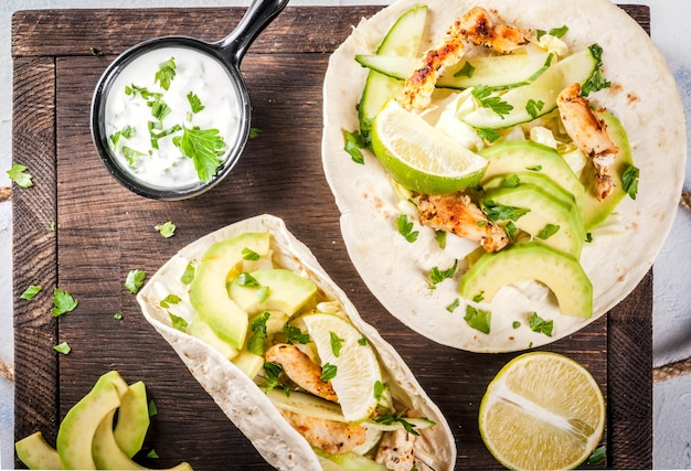 Healthy food snack. tortillas taco with grilled chicken, avocado, fresh salsa, lettuce, lime