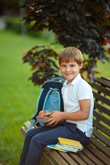 Healthy food for the student. cute boy eating fruit outdoors near school.