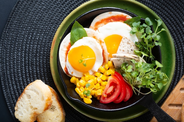 Healthy food super breakfast concept  fried eggs and micro-green salad with corn and tomato in skillet iron pan with copy space