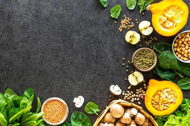 健康食品の表面。コピースペース、上面図と暗い石の表面に秋の新鮮な野菜
