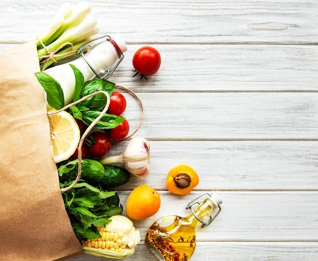 건강 식품 테이블. 종이 봉지, 야채 및 과일의 건강 식품. 쇼핑 식품 슈퍼마켓과 깨끗한 채식주의 자 식사 개념.