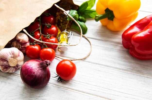 健康食品テーブル。紙袋の健康食品、白い木製のテーブルの上の野菜