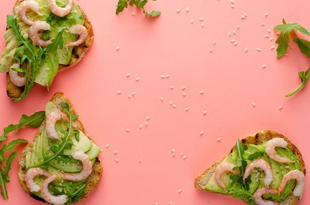 Здоровая пища. тосты с авокадо, креветками и рукколой. вид сверху, плоская планировка, copyspace. фитнес-питание и здоровый образ жизни
