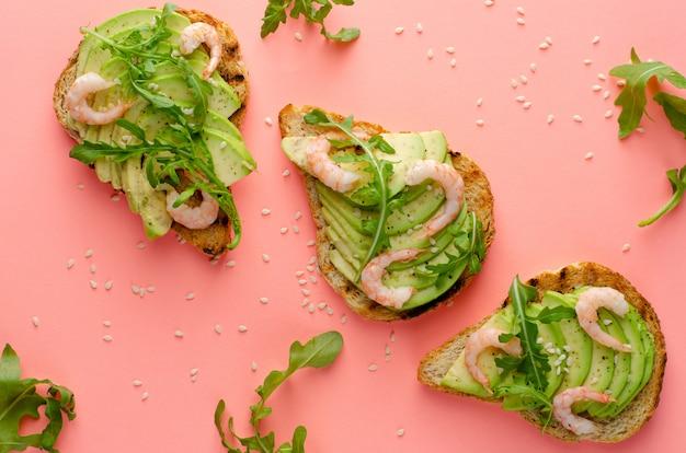 Здоровая пища. тосты с авокадо, креветками и рукколой. вид сверху, плоская планировка. фитнес-питание и здоровый образ жизни