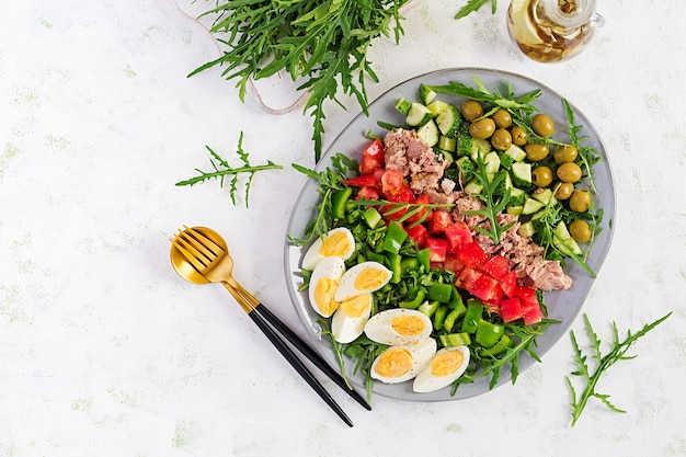 Healthy food. tuna fish salad with eggs, cucumber, tomatoes, olives and arugula.  french cuisine. top view, copy space, flat lay