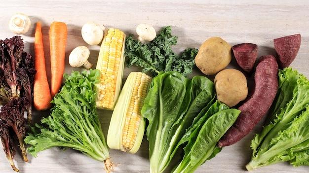 Здоровая пища, различные свежие овощи лист на коричневом мраморном деревянном фоне. вид сверху. копировать пространство. кале, салат, фиолетовый салат, эндивий, морковь, грибы, кукуруза, сладкий картофель, картофель