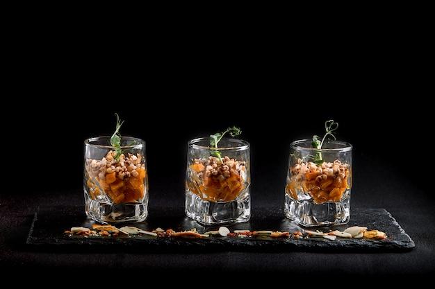 Здоровая еда, веганский вегетарианские мюсли из зеленого гречихи и тыквенных семечек в стеклянном такане. концепция еды fusion, низкий ключ, космос экземпляра.