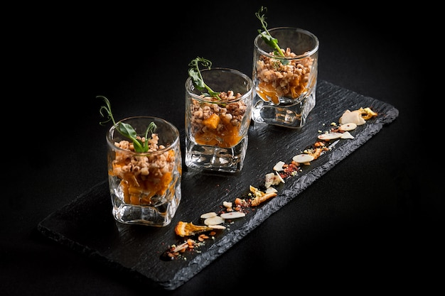 Healthy food, vegan vegetarian muesli made from green buckwheat and pumpkin seeds in a glass takan. fusion food concept, low key, copy space.