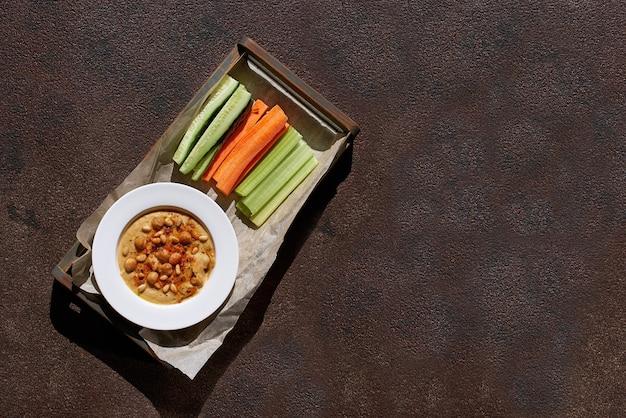 건강한 음식. 식물성 단백질 공급원. 후 무스 그릇, 돌 테이블, 채소, 삶은 병아리 콩