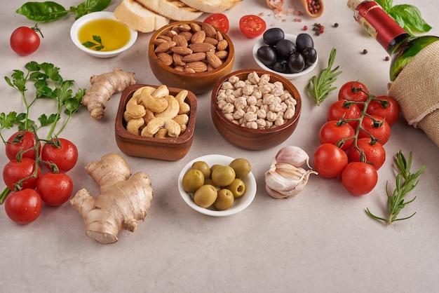 건강한 음식. 콘크리트 표면, 채식 음식 또는 지중해 요리 개념, 복사 공간에 야채, 레몬, 병아리 콩. 과일, 야채, 곡물, 견과류 올리브 오일 나무 테이블에.