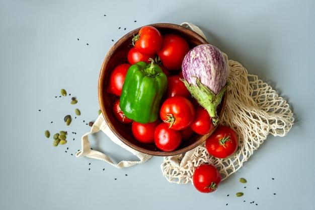 灰色の背景に健康食品野菜。リサイクルテキスタイルバッグの食料品。環境にやさしいプラスチックフリーの低廃棄物ライフスタイル。ゼロウェイストバイオ食品貯蔵とショッピングのコンセプト。