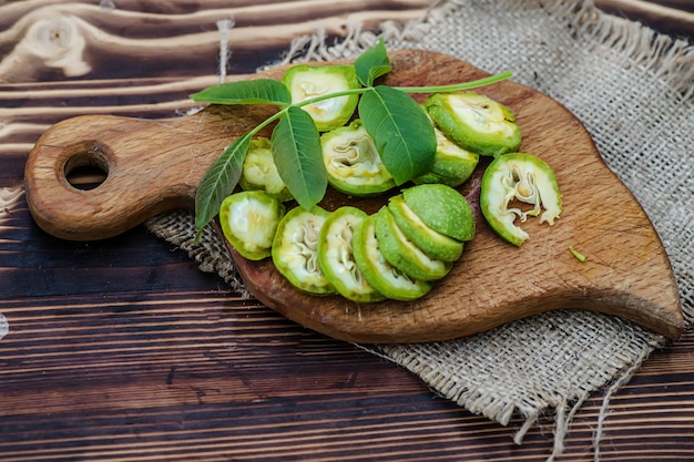 健康食品。まな板の上にくるみをスライスして散らします。古いヴィンテージのテーブルと熟していないクルミの果実全体。フラットレイ。上面図