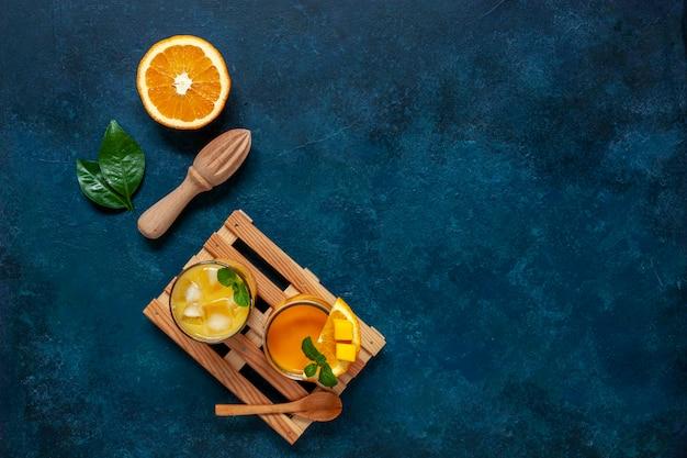 健康食品、健康と減量の概念、天然有機フレッシュマンゴーとオレンジのスムージー。