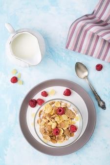Здоровое питание цельнозерновые хлопья с малиной и молоко на синем столе.