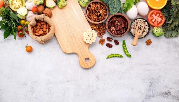 Здоровая пища с деревянной разделочной доской на белом мраморном фоне