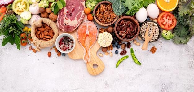 흰색 대리석 배경에 나무 커팅 보드와 함께 건강에 좋은 음식