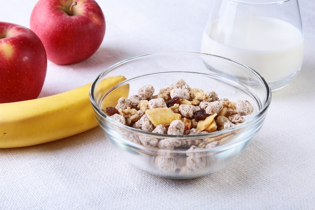 Healthy food with corn flakes cereal in a bowl, apple, banana and glass with milk. morning breakfast.