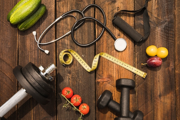 Healthy food with exercise equipment; measuring tape and stethoscope