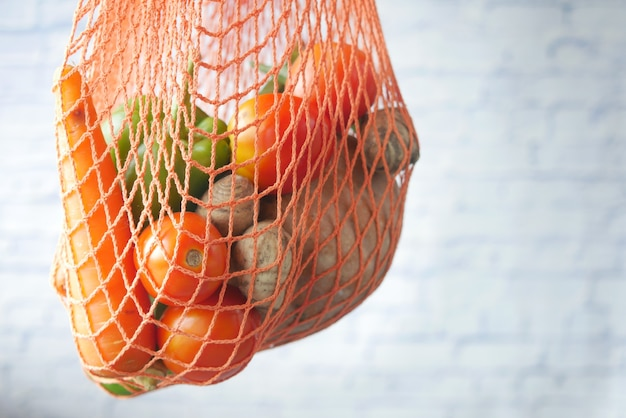 白い背景の上の紙の再利用可能なバッグ野菜と健康食品