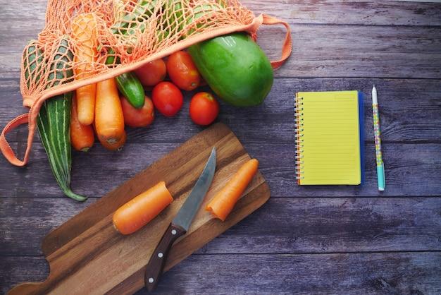 Здоровая еда с бумажным многоразовым пакетом с овощами и блокнотом на столе