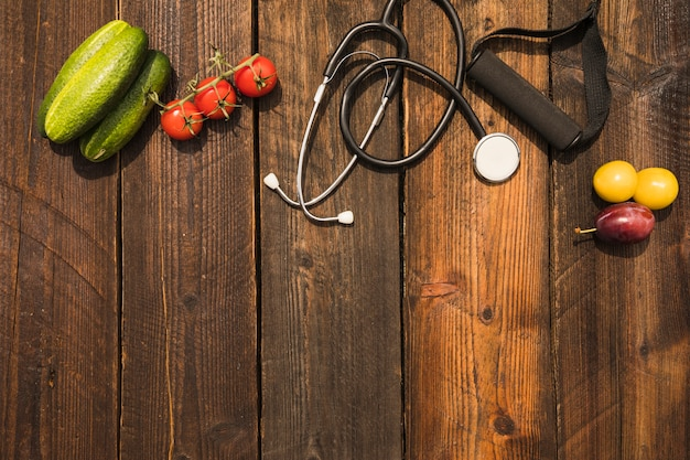 Healthy food with stethoscope and fitness strap on wooden backdrop