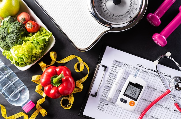 Healthy food with weight scale, sports shoes, dumbells and measure tape