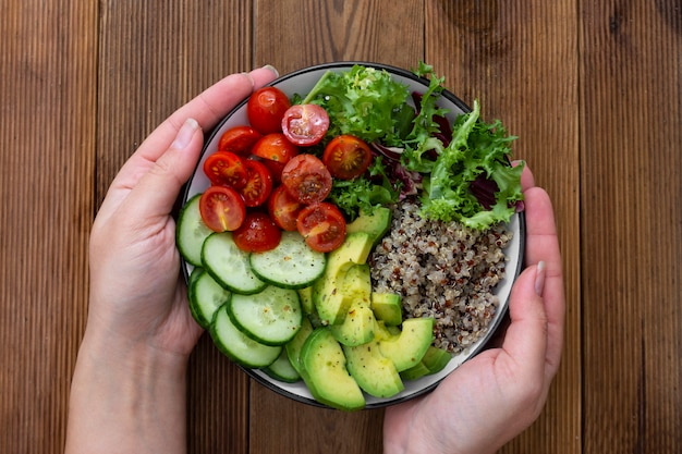 Healthy food. womans hand holding budha bowl with quinoa, avocado, cucumber, salad, tomatoe, olive oil.