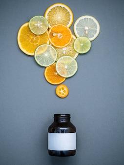 건강 식품 및 의학 개념. 혼합 감귤 류 과일 회색 배경 평평하다에 슬라이스.