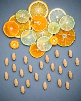 Healthy foods and medicine concept.  Mixed citrus fruits sliced on gray background flat lay.