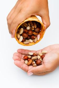 白い背景の側面図の健康食品のコンセプト。男は手のひらにミックスナッツを注ぐ。