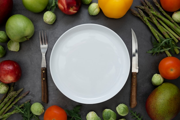 Healthy foods or diet concept. empty round plate with different fruits and vegetables arround. flat lay.