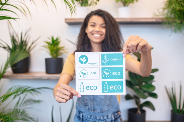 Здоровая еда. счастливая женщина показывает плакат с символами полезных продуктов в протянутых руках, стоя возле комнатных растений