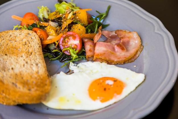 샐러드와 함께 건강하고 신선한 아침 식사; 베이컨; 반 튀긴 계란과 회색 접시에 토스트