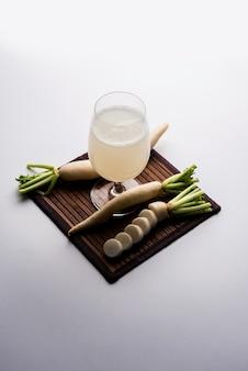 Напиток с соком healthy fresh или экстрактом мули в стакане с сырым мулом