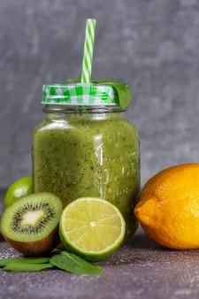 회색 콘크리트 배경에 키위 라임과 레몬으로 둘러싸인 건강한 신선한 과일 스무디 음료. 건강한 생활 습관과 적절한 영양의 개념. 비타민 음료.