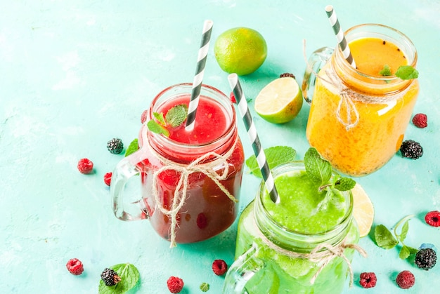 Healthy fresh fruit and veggie smoothies with ingredients on light blue concrete table,